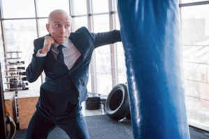 an angry bald businessman beats a boxing pear in t MJX7H2Z 1